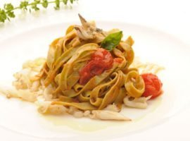 Basil tagliatelle on a cherry tomato and baby squid sauce